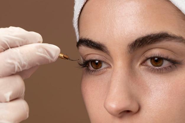 Mulher fazendo tratamento de cílios para o cliente