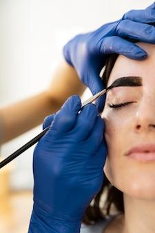 Mulher fazendo tratamento para a sobrancelha em um salão de beleza