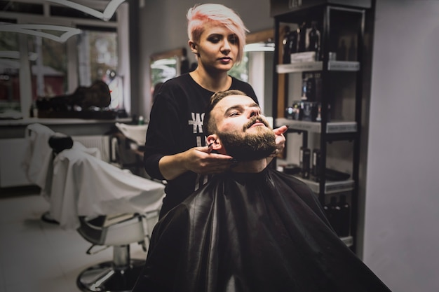Mulher fazendo tratamento para cliente na barbearia