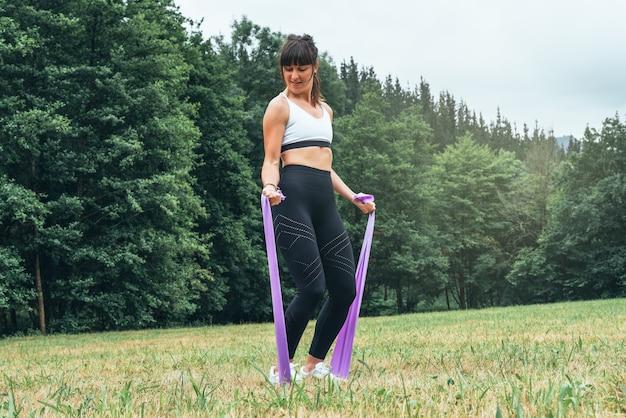 Mulher fazendo treinamento de força com um elástico no meio de uma floresta