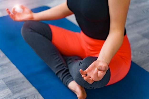 Mulher fazendo treinamento físico, close-up de jovem exercitar e sentado em posição de lótus yoga
