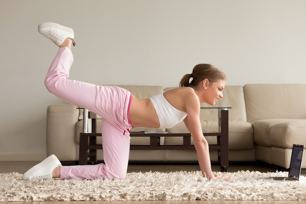 Mulher fazendo um exercício de kickback do joelho em casa