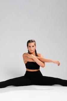 Mulher fazendo um exercício dividido e copie o espaço