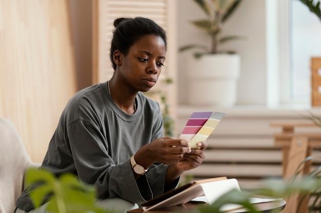 Mulher fazendo um plano usando paleta de cores e tablet para redecorar a casa
