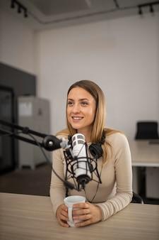 Mulher fazendo um podcast no rádio com um microfone