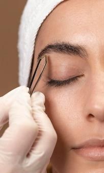 Mulher fazendo um tratamento de sobrancelha para seu cliente