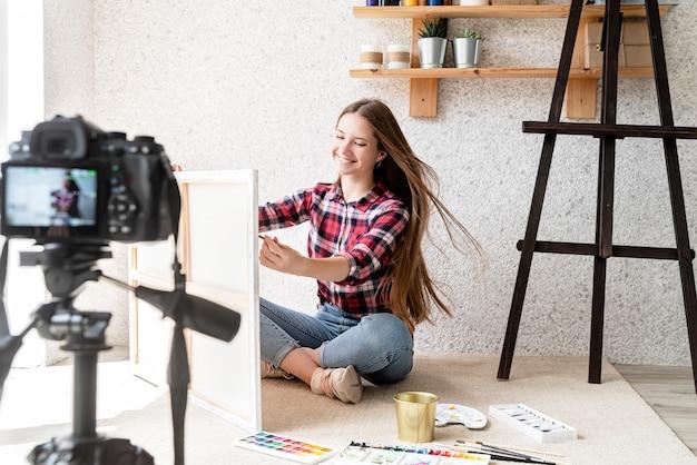 Mulher fazendo um vídeo para o seu blog sobre arte usando uma câmera digital montada em tripé
