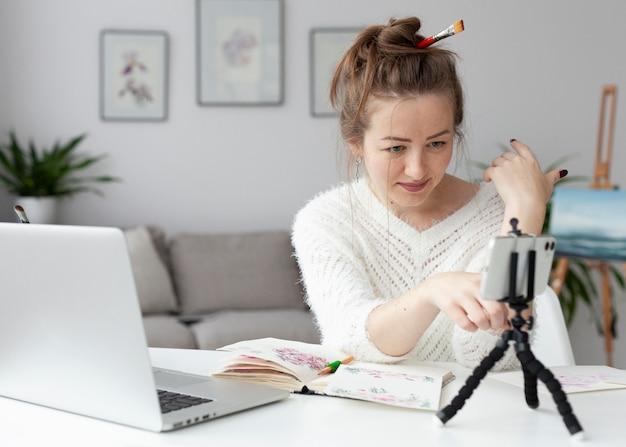 Mulher fazendo um vlog de arte em casa com o telefone