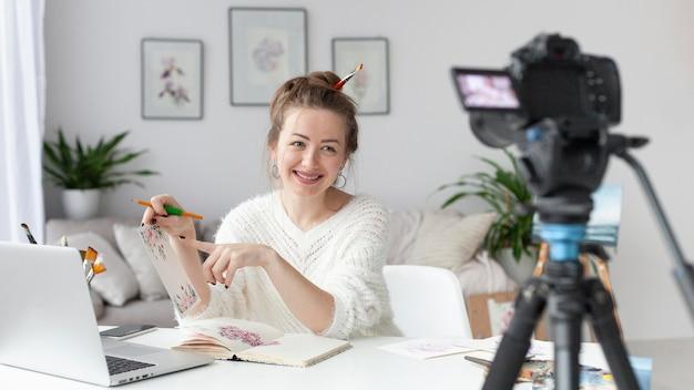 Mulher fazendo um vlog de arte em casa