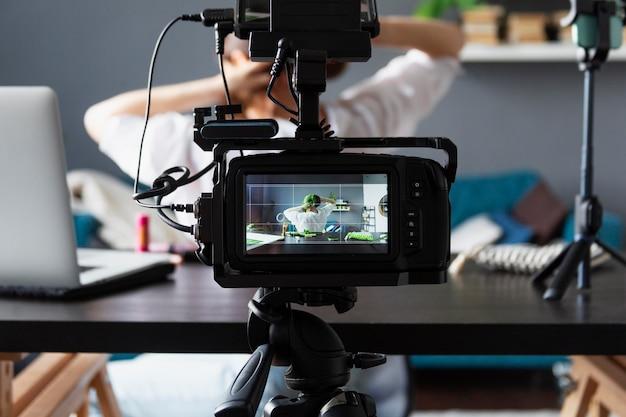 Mulher fazendo um vlog de beleza com sua câmera profissional