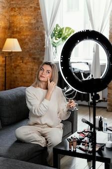 Mulher fazendo um vlog de beleza em casa
