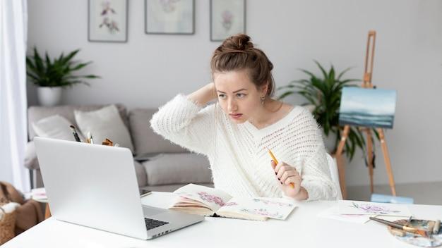 Mulher fazendo um vlog em casa com seu laptop