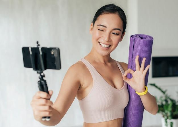 Mulher fazendo um vlog segurando seu tapete de ginástica