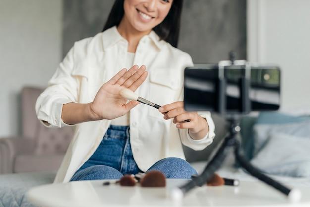 Mulher fazendo um vlog sobre maquiagem dentro de casa