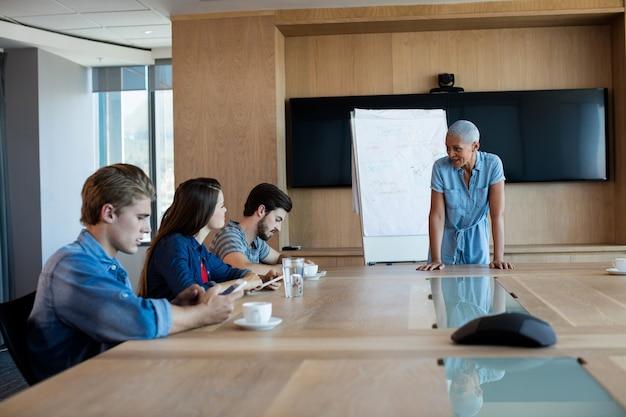 Mulher fazendo uma apresentação para os colegas na sala de conferências do escritório