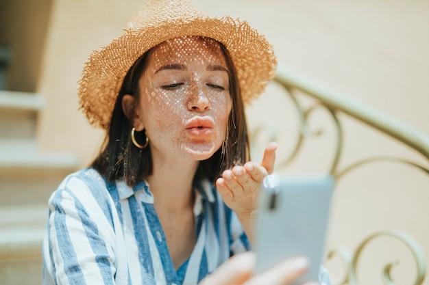 Mulher fazendo uma chamada de vídeo do seu telefone