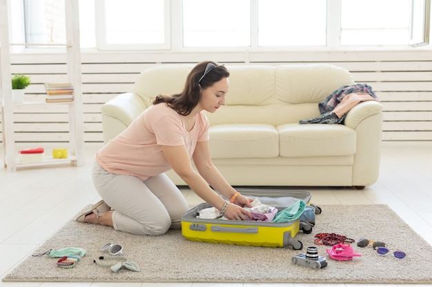 Mulher fazendo uma mala amarela em casa