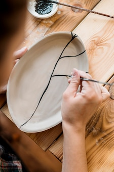 Mulher fazendo uma obra-prima de cerâmica