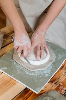 Mulher fazendo uma panela de barro em sua oficina