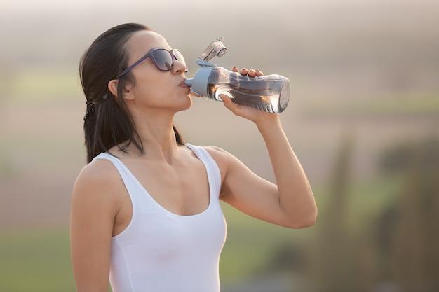 Mulher fazendo uma pausa para beber da garrafa de água durante uma caminhada e postes em pé no cume de uma montanha rochosa, olhando para os vales.