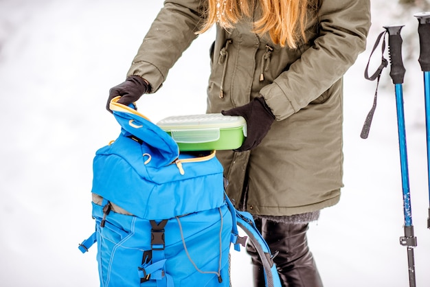 Mulher fazendo uma pausa pegando uma lancheira da mochila na floresta de neve durante uma caminhada de inverno