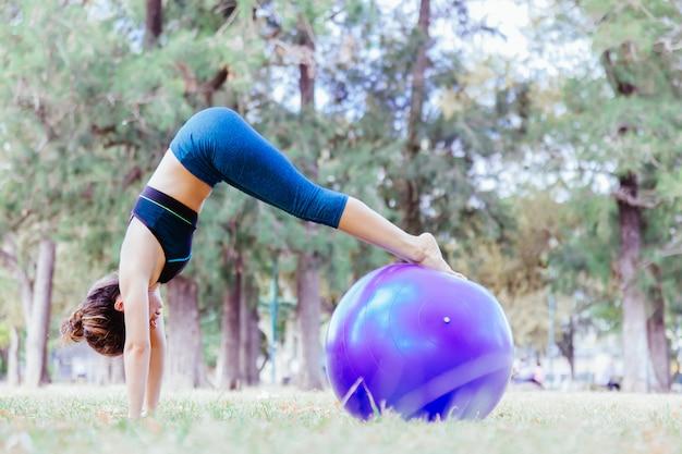 Mulher fazendo uma pose de ioga golfinho acima de uma bola grande ao ar livre. estilo de vida saudável de pilates para as pessoas. treinar ao ar livre e ficar em forma conceito. pessoas fazendo bem-estar meditação no parque.