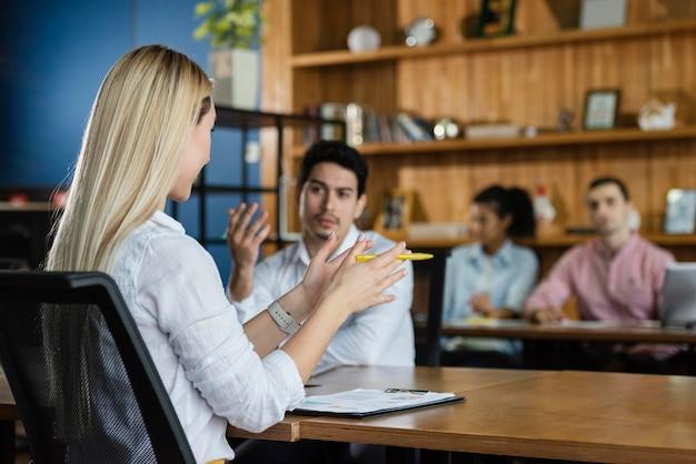 Mulher fazendo uma reunião no local de trabalho com outras pessoas
