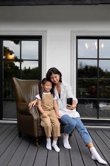 Mulher fazendo uma videochamada com o marido ao lado da filha ao ar livre