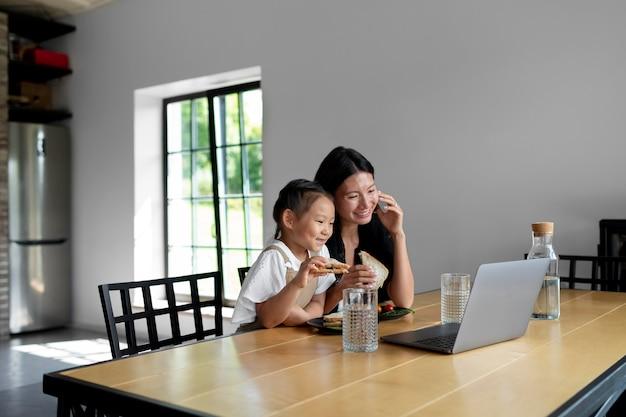 Mulher fazendo uma videochamada com o marido ao lado da filha dentro de casa
