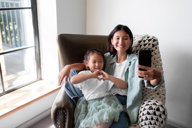 Mulher fazendo uma videochamada com o marido ao lado da filha