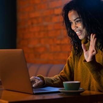Mulher fazendo uma videochamada em um café