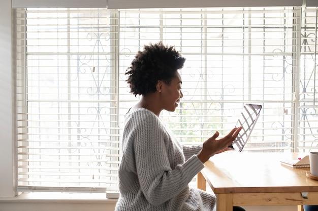 Mulher fazendo uma videochamada em um tablet durante covid19