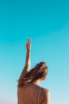 Mulher fazendo v suspirar no céu