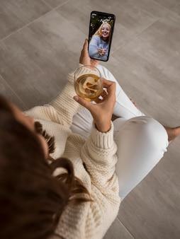 Mulher fazendo videochamadas com amigos em quarentena com bebida