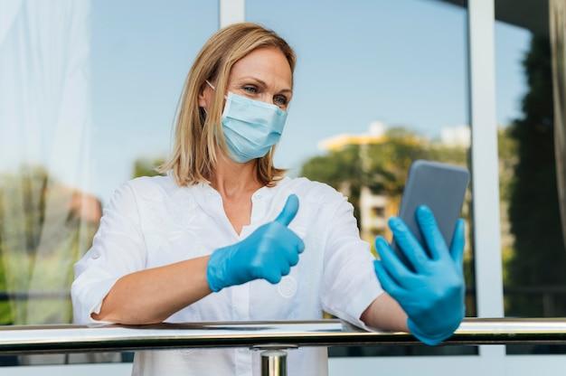 Mulher fazendo videochamadas de casa com máscara médica e luvas