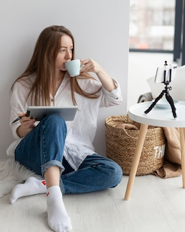 Mulher fazendo vlogs com o telefone dentro de casa