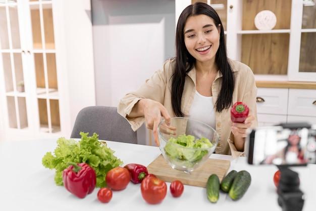 Mulher fazendo vlogs em casa com vegetais e smartphone