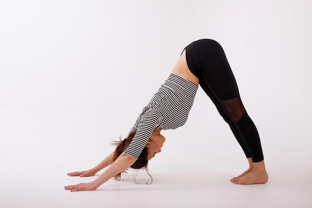 Mulher fazendo yoga em um fundo branco. cachorro asana. dia internacional da ioga