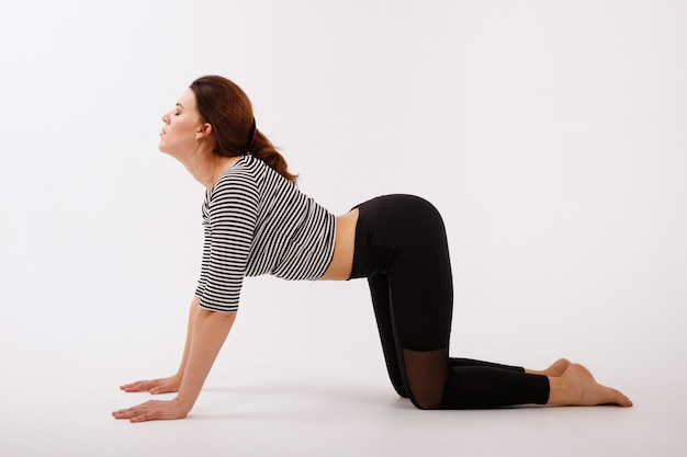 Mulher fazendo yoga em um fundo branco. gato asana. meditação. dia internacional da ioga