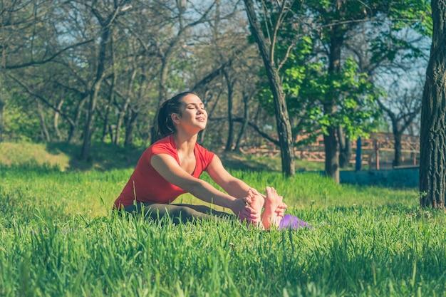 Mulher fazendo yoga na grama verde