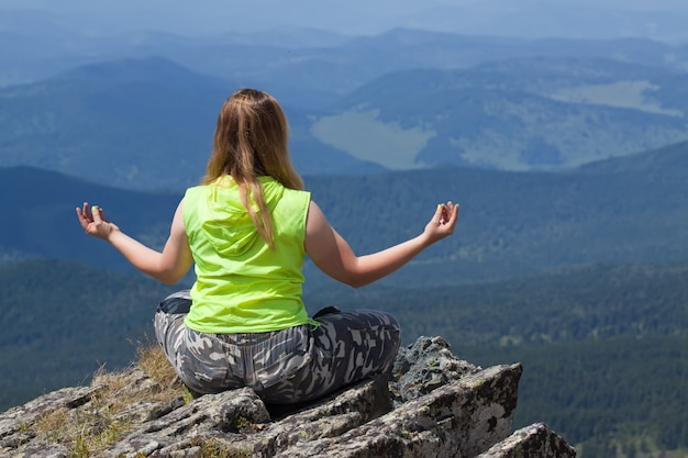 Mulher fazendo yoga na montanha