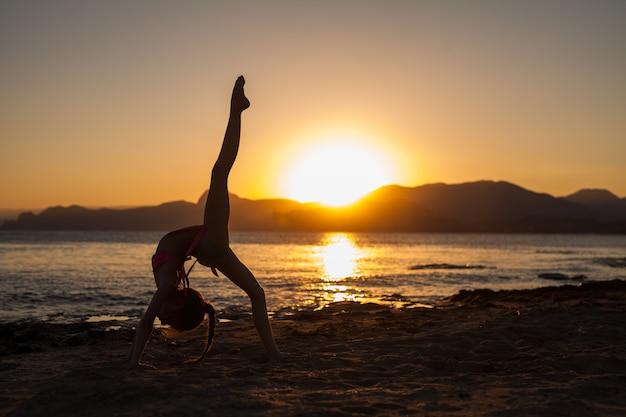 Mulher fazendo yoga na natureza ao ar livre ao nascer do sol