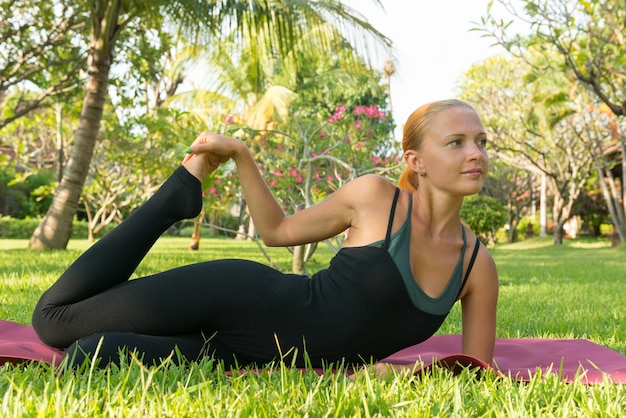 Mulher fazendo yoga no jardim