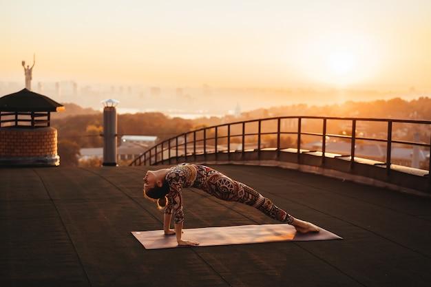 Mulher fazendo yoga no telhado de um arranha-céu na cidade grande.