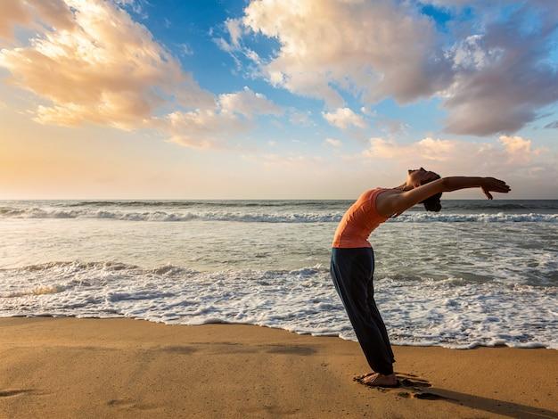 Mulher fazendo yoga saudação ao sol surya namaskar