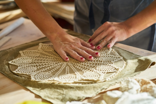 Mulher, fazer, padrão, ligado, prato cerâmico, mãos, close-up,