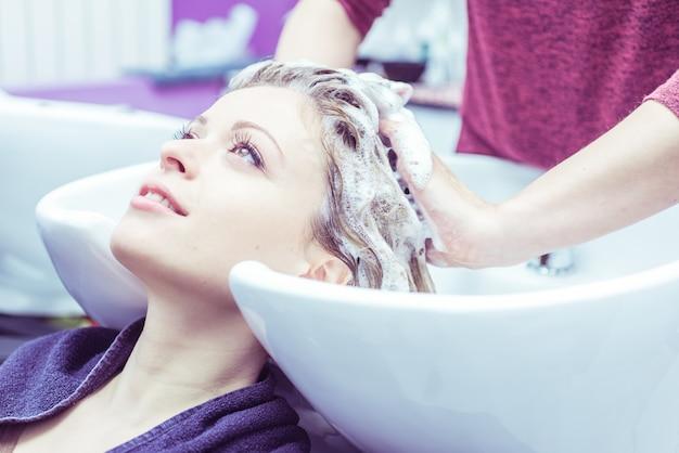 Mulher fazer xampu no cabeleireiro