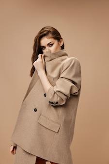 Mulher fecha com casaco bege e olha para a frente vista lateral
