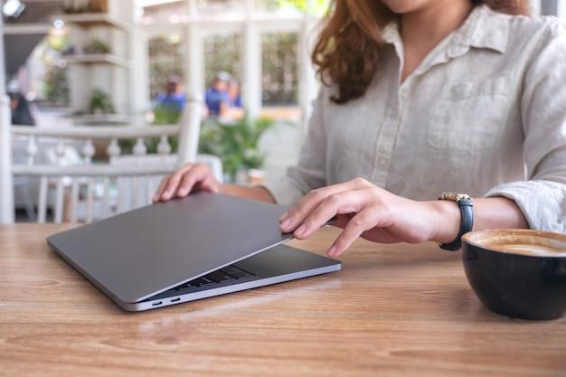 Mulher fecha e abre um laptop na mesa após terminar de usá-lo