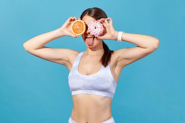 Mulher fechando os olhos com um donut rosa e metade de uma suculenta toranja, se divertindo mostrando a língua